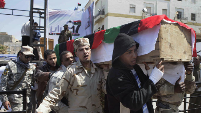 Libyan rebels carry the coffin of a comrade, whom they said was killed by forces loyal to Moammar Gadhafi in Brega, during a funeral in Benghazi, Tuesday, April 19, 2011. Europe is ready to send an armed force to Libya to ensure delivery of humanitarian aid and Britain said Tuesday it will dispatch senior military officers to advise the opposition _ signs that Western nations are inching closer to having troops on Libyan soil. (AP Photo)