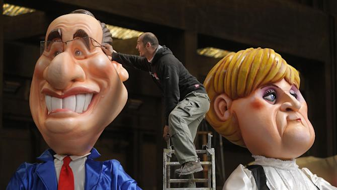 """A worker puts the final touches to giants figures depicting French President Francois Hollande, left, and German Chancellor Angela Merkel during preparations for the 129th Nice carnival parade, Tuesday, Feb. 12, 2013, in Nice, southeastern France. The 129th Nice Carnival runs from February 15th  until March 6th and will celebrate the theme """"King of the five continents"""" . (AP Photo/Lionel Cironneau)"""