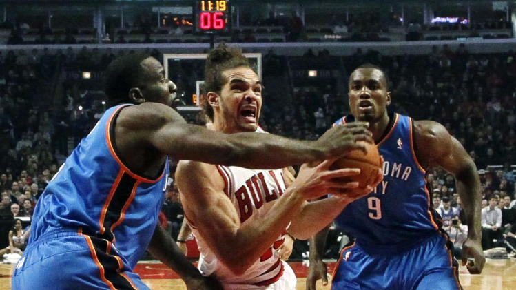 Chicago Bulls center Joakim Noah (13) drives the lane between Oklahoma City Thunder center Kendrick Perkins, left, and Serge Ibaka (9) during the first half of an NBA basketball game, Thursday, Nov. 8, 2012, in Chicago. (AP Photo/Charles Rex Arbogast)