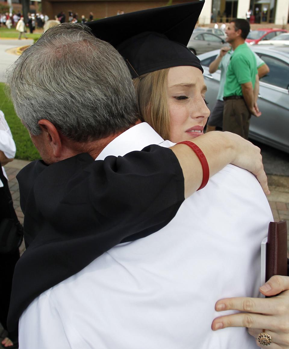 Brooke Lofton, one of Morgan Sigler's friends, hugs Morgan's father, Allan Sigler, after the graduation ceremonies on Saturday, Aug. 6, 2011 in Tuscaloosa, Ala.  Morgan lost her life when a tornado ripped through Tuscaloosa on April 27, 2011. (AP Photo/Butch Dill)