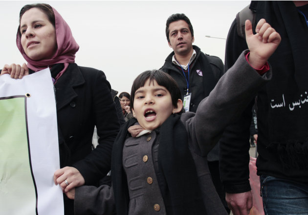 An Afghan girl, center, walks with her mother during a march calling for an end to violence against women, in Kabul, Afghanistan, Thursday, Feb. 14, 2013. Dozens of Afghan activists have marked Valent