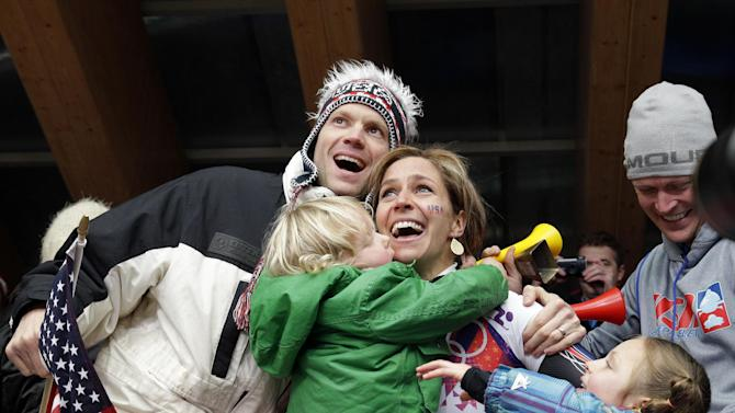 ADDS ID OF MAN AT LEFT - Noelle Pikus-Pace of the United States celebrates with her brother Jared Pikus, left, husband, Janson Pace, far right, and children, Traycen, left, and Lacee, right, after she won the silver medal during the women's skeleton competition at the 2014 Winter Olympics, Friday, Feb. 14, 2014, in Krasnaya Polyana, Russia. (AP Photo/Michael Sohn)