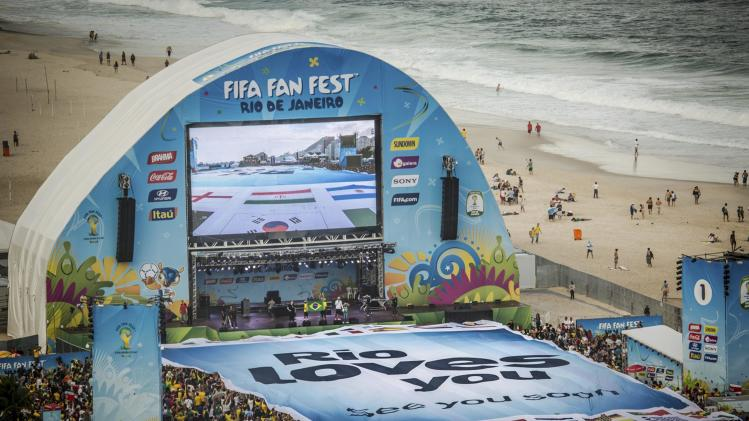Soccer fans stretch a giant sign placed at the FIFA Fan Fest by the City Hall in Rio de Janeiro