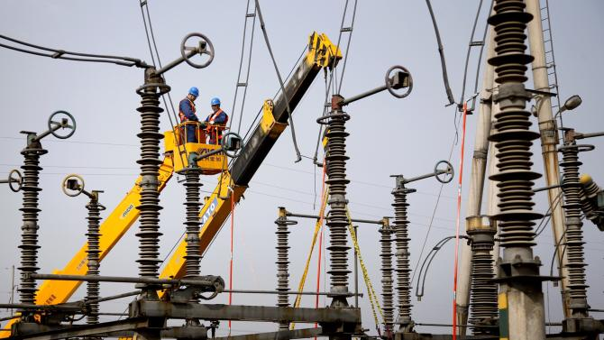 Employees inspect the equipment at an electric power transformation substation in Handan