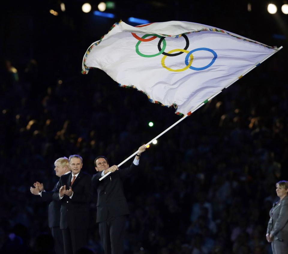Rio de Janeiro mayor Eduardo Paes waves the olympic flag next to Jacques Rogge and London Mayor Boris Johnson, left, during the Closing Ceremony at the 2012 Summer Olympics, Sunday, Aug. 12, 2012, in London. (AP Photo/Kristy Wigglesworth)