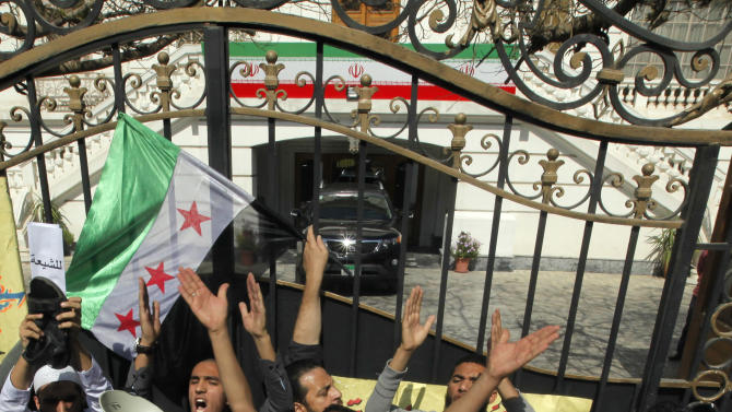 Dozens of mostly ultraconservative protesters shout anti-Iran slogans and wave a Syrian revolution flag during a protest at the residence of Iran's top diplomat to protest the Egyptian government's attempt to improve ties with Tehran in Cairo, Egypt, Friday, April 5, 2013. The Iranian flag is seen at background. (AP Photo/Amr Nabil)