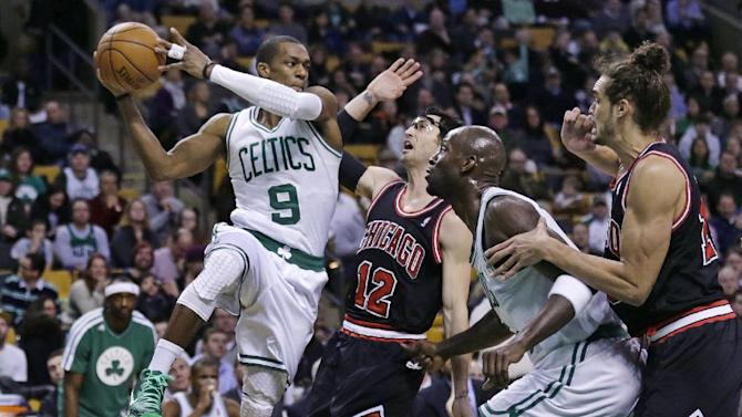 Boston Celtics guard Rajon Rondo (9) looks to pass as he is pressured by Chicago Bulls guard Kirk Hinrich (12) during the first half of an NBA basketball game in Boston on Friday, Jan. 18, 2013. At right are Celtics forward Kevin Garnett and Bulls center Joakim Noah. (AP Photo/Charles Krupa)