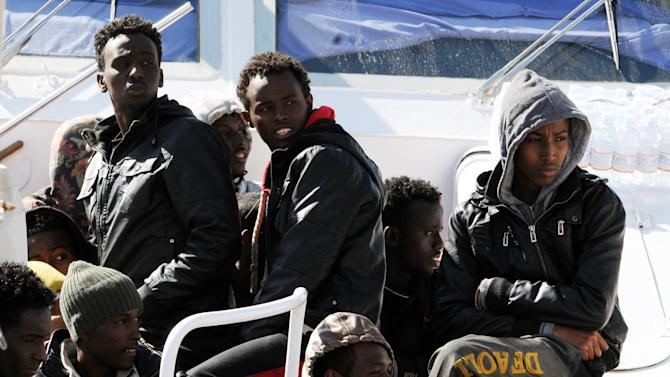 Migrants sit on the deck of an Italian Coastal Guard boat as they wait to disembark at Palermo's harbor, Italy, after being rescued at sea, Saturday, April 18, 2015. Italian ships have picked up some 10,000 people, many of them refugees of war and persecution, over the past week, an unprecedented number in such a short period. The influx is putting pressure on Italy's shelter system and raising calls for a better response to the emergency. (AP Photo/Alessandro Fucarini)
