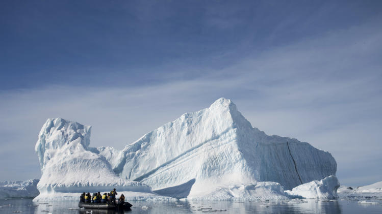 In this Dec. 1, 2009 photo provided by Aurora Expeditions, an inflatable boat carries tourists past an iceberg along the Antarctic Peninsula. In a remote, frozen, almost pristine land where the only human residents are involved in research, tourism comes with risks, for both the continent and the tourists. (AP Photo/Aurora Expeditions, Andrew Halsall) EDITORIAL USE ONLY