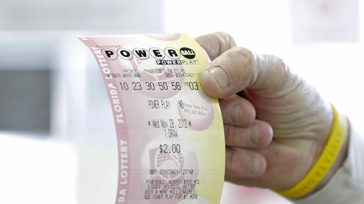 FILE - This Nov. 28, 2012, file photo shows a customer at a 7-Eleven convenience store with a Powerball ticket in Tampa, Fla. The jackpot for the latest drawing on Wednesday, May, 15, 2013, has ballooned to an estimated $360 million, with a cash value of $229.2 million, making it the third largest Powerball jackpot and the seventh largest jackpot ever. (AP Photo/Chris O'Meara, File)