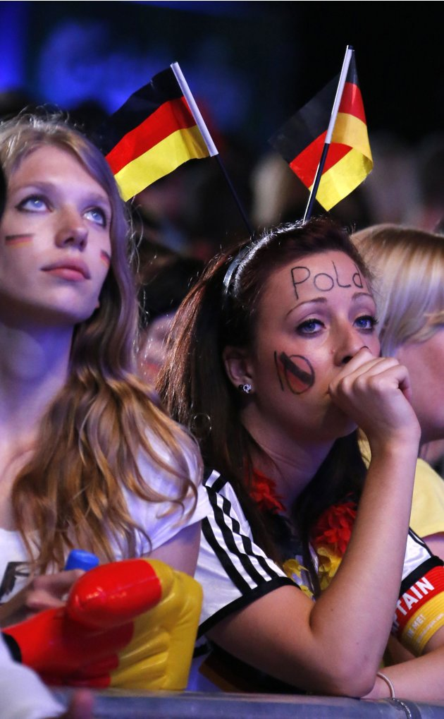 German soccer fans react during a public screening, while they watch their team play against Italy in their Euro 2012 semi-final soccer match, in Berlin