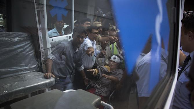 Indian woman Dalimi Baishya, on wheel chair, who was injured in Saturday's earthquake while on a pilgrimage to Nepal is assisted by others to enter an ambulance after she arrived at the airport in Gauhati, India, Monday, April 27, 2015. The earthquake was the worst to hit the South Asian nation in more than 80 years. It and was strong enough to be felt all across parts of India, Bangladesh, China's region of Tibet and Pakistan. (AP Photo/ Anupam Nath)