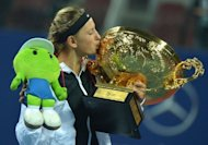 Victoria Azarenka of Belarus kisses her trophy after winning the women's singles final against Maria Sharapova of Russia at the China Open tennis tournament. Azarenka won 6-3, 6-1