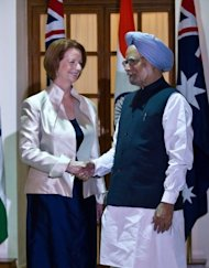 <p>Australian Prime Minister Julia Gillard (L) shakes hands with Indian Prime Minister Manmohan Singh prior to a meeting in New Delhi, on October 17. Gillard met her Indian counterpart to start negotiations on the sale of uranium to energy-starved India for its nuclear power programme.</p>