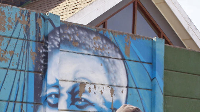 A man looks back as he walk past a mural of former South African president Nelson Mandela in the town of Umtata, South Africa, Friday, June 28, 2013. Members of Nelson Mandela's family as well as South African Cabinet ministers have visited the hospital where the 94-year-old former president is critically ill. (AP Photo/Schalk van Zuydam)