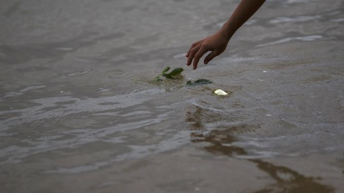 A boy places a rose into a sea near a wave-shaped tsunami monument for victims of the 2004 tsunami in Ban Nam Khem