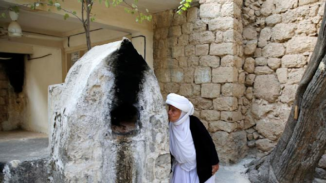 A displaced woman from the minority Yazidi sect, who fled violence in the Iraqi town of Sinjar, worships at their main holy temple Lalish in Shikhan