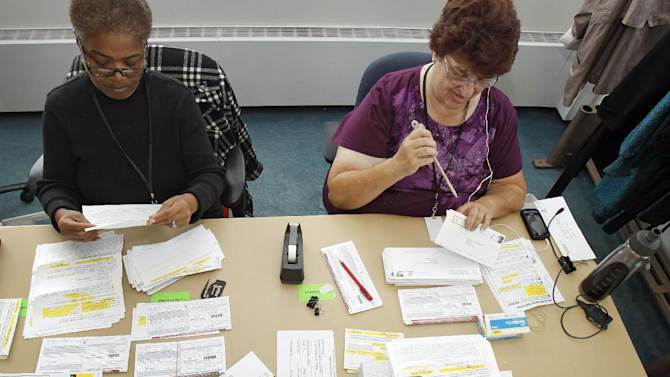 FILE - In this Sept. 28, 2012, file photo Cheryl Banks, left to right, and Genny Armstrong open and process vote-by-mail applications in Cleveland, Ohio, in preparation for early voting for November presidential election. Five weeks to Election Day, President Barack Obama is within reach of the requisite 270 Electoral College votes needed to win a second term according to an Associated Press analysis. Mitt Romney can still prevail in the race to amass the necessary votes, but his path to victory has become much narrower. To overtake Obama, the Republican challenger would need to quickly gain the upper hand in nearly all of the nine states where he and Obama are competing the hardest. (AP Photo/Tony Dejak, File)
