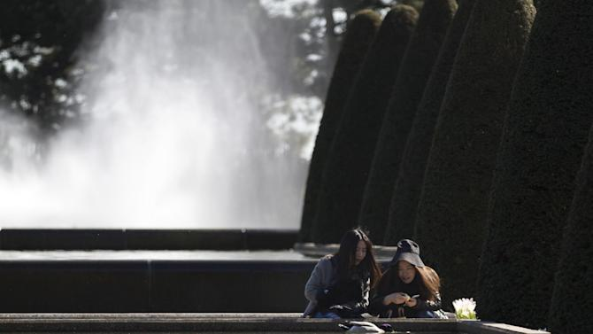 Two tourists feed a duck in a pond at Keukenhof, known as the Garden of Europe, a spring park with approximately seven million flower bulbs, in Lisse, Netherlands, Tuesday, April 21, 2015. (AP Photo/Peter Dejong)