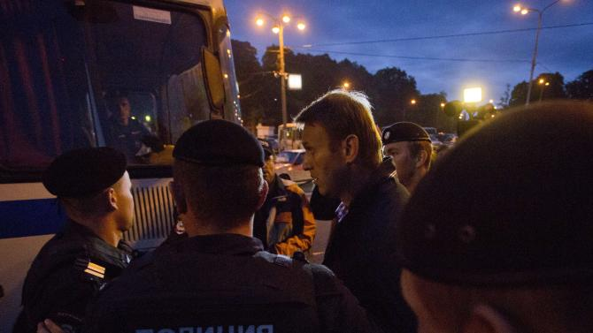 Russian police officers detain Alexei Navalny, center, after his meeting with supporters in Sokolniki park in Moscow, late Sunday, Aug. 25, 2013. Alexei Navalny, the anti-corruption blogger and a leader of the Russian protest movement, will face the incumbent Sergei Sobyanin, who has proven an invisible candidate rarely spotted on the debate floor or shaking hands with voters, in the upcoming Moscow's mayor election on Sept. 8. (AP Photo/Evgeny Feldman)