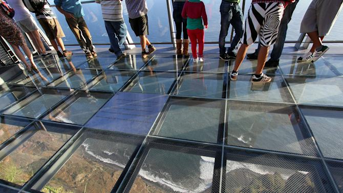 In this photo taken Oct. 31, 2012, people visit the Portuguese Madeira Islands regional government's latest showpiece investment, a panoramic steel-and-glass viewing point perched on what claims to be Europe's highest cliff-top in Cabo Girao, Portugal. The price tag for the platform, parking lot and cafe was euro 2.5 million. That's a hefty outlay for a near-bankrupt archipelago of about 250,000 people which has euro 6.3 billion in public debt, needed a euro 1.5 billion bailout last year and has promised to be frugal. But development funds from the European Union, bankrolled by the continent's taxpayers, made it affordable by picking up euro 2 million of the tab. (AP Photo/Joana Sousa)
