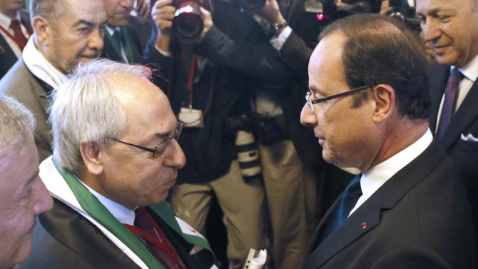 French President Francois Hollande, right, shakes hands with the leader of the Syrian National Council (SNC), Abdulbaset Sieda during the Friends of Syria conference, Friday, July 6, 2012 in Paris. The United States and its European partners are threatening new sanctions on Syrian President Bashar Assad's regime if he doesn't act fast on a new peace plan, but the fractured and frustrated Syrian opposition is seeking quick military actions instead. (AP Photo/Patrick Kovarik, Pool)