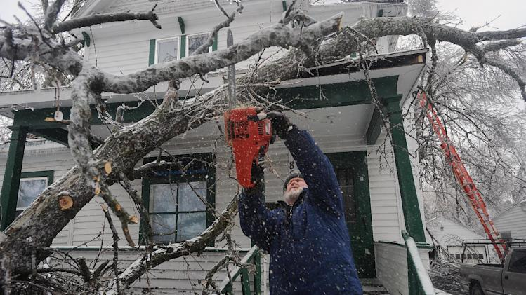 Tom Jandl removes branches from a fallen tree on his rental property at the corner of 13th Street and Prairie Avenue Wednesday, April 10, 2013 in Sioux Falls, S.D. (AP Photo/Argus Leader, Jay Pickthorn) NO SALES
