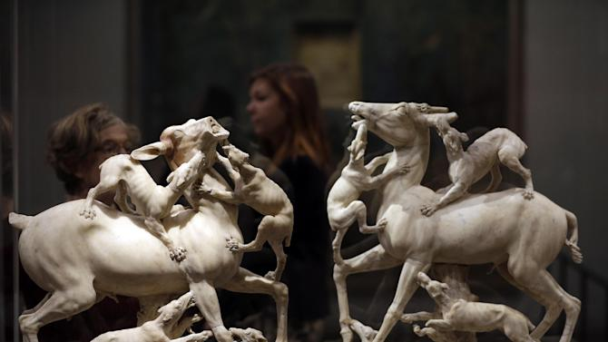 Visitors walks past marble sculptures of stags being attacked by hunting dogs, found in the ruins of ancient Roman town of Herculaneum, during a photo call for the upcoming exhibition entitled 'Life and death Pompeii and Herculaneum', in central London, Tuesday, March 26, 2013. The exhibition about the two Roman cities, buried by a catastrophic volcanic eruption of Mount Vezuvius in 79 AD, will run at the museum from March 28 to Sept. 29, 2013. (AP Photo/Lefteris Pitarakis)