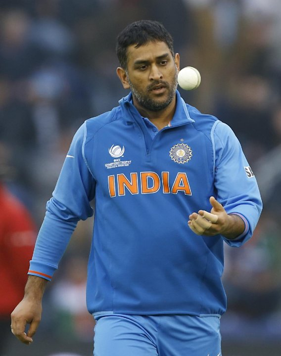 India's MS Dhoni prepares to bowl during the ICC Champions Trophy semifinal between India and Sri Lanka at the Cardiff Wales Stadium in Cardiff, Thursday, June 20, 2013