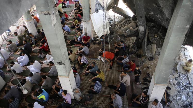 Palestinians attend Friday prayers conducted among the ruins of a mosque in Rafah