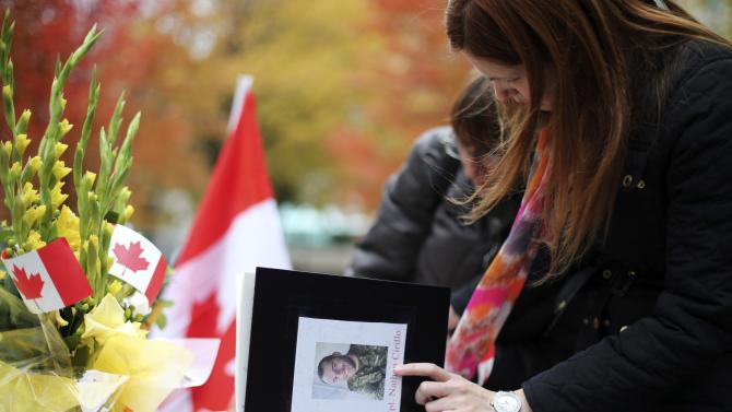 People write in books of condolence for fallen Canadian soldiers, Warrant Officer Vincent and Corporal Cirillo during a vigil in Montreal