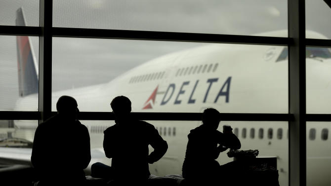 Travelers on Delta Airlines waits for flights Monday, Oct. 29, 2012, in Detroit. Dozens of departing flights have been canceled at Detroit Metropolitan Wayne County Airport as a looming superstorm locks down flights to the East Coast. Hurricane Sandy continued on its path Monday, as the storm forced the shutdown of mass transit, schools and financial markets, sending coastal residents fleeing, and threatening a dangerous mix of high winds and soaking rain. (AP Photo/Charlie Riedel)