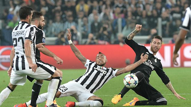 Juventus' Arturo Vidal, center, challenges for the ball with Real Madrid Sergio Ramos, right, during the Champions League, semifinal soccer match between Juventus and Real Madrid at the Juventus Stadium in Turin, Italy, Tuesday, May 5, 2015. (AP Photo/Massimo Pinca)