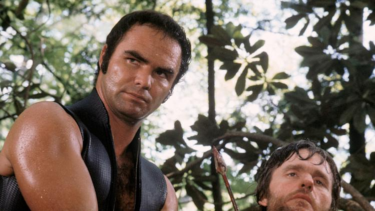 "This image released by Warner Bros. Entertainment shows actor Burt Reynolds portraying Lewis Medlock, left, and Bill McKinney as Don Job in the 1972 film ""Deliverance."" Four decades ago, the lush northeast Georgia mountains were introduced to the world in the hit film ""Deliverance.""  Though many in the region still bristle at the movie's portrayal of locals as uneducated, toothless hillbillies who sodomize visitors from the big city, the film helped create the $20 million rafting and outdoor sports industry along the Chattooga River, which splits Georgia and South Carolina and was the fictional Cahulawassee River in the movie. That's why the communities along the Chattooga are celebrating the 40th anniversary of the movie's release with this weekend's first ever Chattooga River Festival.  (AP Photo/Warner Bros. Entertainment)"