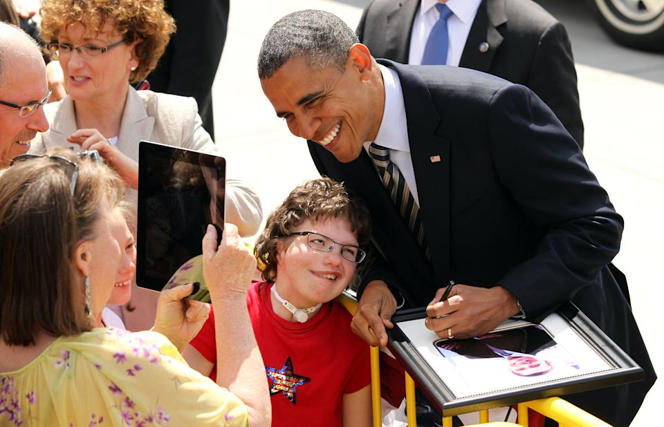 President Barack Obama poses for a photo with Myra Soukup, 16, center, as Jane Soukup, left, makes the image with an iPad, upon his arrival in Minneapolis, Friday, June 1, 2012, for an event on the economy at Honeywell, followed by a campaign event. (AP Photo/Genevieve Ross)
