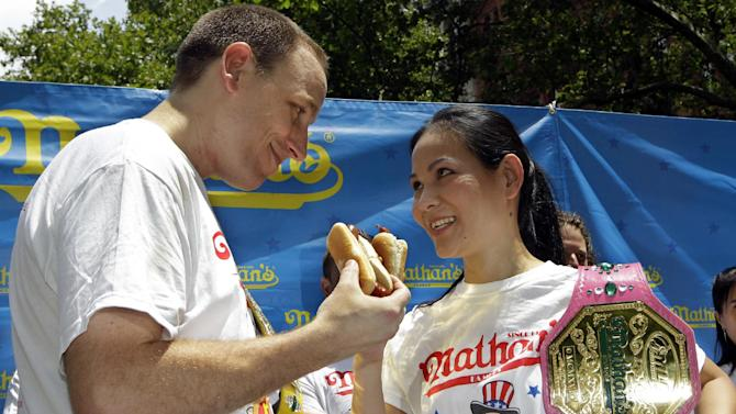 "FILE - In this July 3, 2012, file photo, hot-dog eating champions Joey Chestnut, left, and Sonya ""The Black Widow"" Thomas pose for photographers at City Hall Park in New York, during a weigh-in for contestants in the annual Coney Island Fourth of July international hot-dog eating contest. The pair aim to take the crowns again at the annual Fourth of July contest on Coney Island.(AP Photo/Kathy Willens, File)"