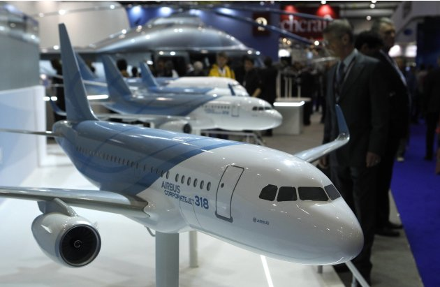 A visitor looks at replica aircrafts on the Airbus booth during the Annual European Business Aviation Convention & Exhibition at Cointrin airport in Geneva