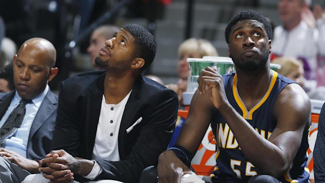 From left, Indiana Pacers assistant coach Popeye Jones, injured guard Paul George and center Roy Hibbert watch from the bench as time runs out in the fourth quarter against the Denver Nuggets in an NBA basketball game Saturday, Dec. 20, 2014, in Denver. The Nuggets won 76-73. (AP Photo/David Zalubowski)