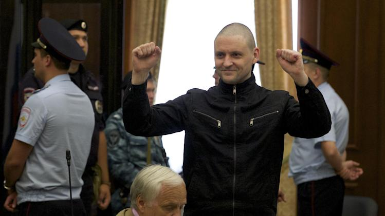 Russian opposition activist Sergei Udaltsov gestures in a court room prior to a hearing in the Bolotnaya square protest trial in Moscow, Russia, Thursday, July 24, 2014. Sergei Udaltsov and Leonid Razvozzhayev are waiting for the sentence Thursday in the Moscow city court on charges of organizing mass riots and colluding to commit a crime. They both pleaded not guilty in a trial that has dragged on since October 2012, when they were detained and put under house arrest. (AP Photo/Ivan Sekretarev)