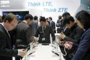 Visitors look at devices at ZTE booth at the Mobile World Congress in Barcelona