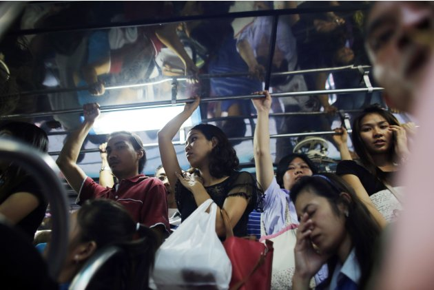 Commuters travel on an overcrowded bus during the evening rush hour in Bangkok