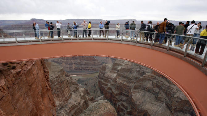 FILE - in this March 20, 2012 file photo, people walk on the Grand Canyon Skywalk during the First Walk event at the Grand Canyon on the Hualapai Indian Reservation at Grand Canyon West, Ariz. On Friday, Oct. 19, 2012, Las Vegas developer David Jin's attorneys will argue before the 9th Circuit U.S. Court of Appeals in San Francisco that the Hualapai tribal court system is manipulated by members of the Tribal Council, hasn't given Jin a fair shot and that he shouldn't have to fight his legal battles there. (AP Photo/Ross D. Franklin, File)