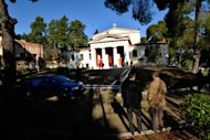Onlookers and police gather outside the antiquities museum in Ancient Olympia where two masked armed robbers tied up a guard and made off with dozens of artifacts, Olympia, southern Greece, Friday, Feb. 17, 2012. Friday's robbery is the second major museum theft in the past two months in Greece. In January, thieves made off with art works by 20th century masters Pablo Picasso and Piet Mondrian from the country's National Gallery in central Athens. (AP Photo/Dimitris Papaioannou)