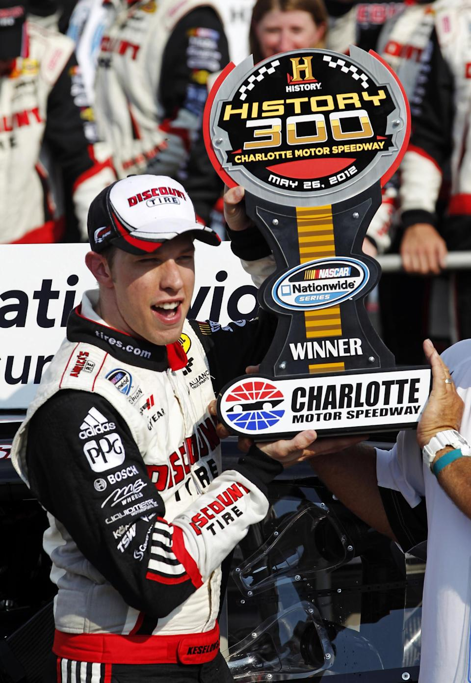 Brad Keselowski holds the trophy in victory lane after winning the NASCAR History 300 Nationwide Series auto race in Concord, N.C., Saturday, May 26, 2012. (AP Photo/Terry Renna)