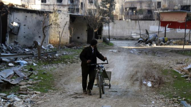 A man walks with his bicycle in a damaged area in the Damascus suburb of Harasta