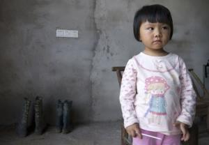 Xu Yilin, whose blood, according to family, has been shown to have almost three times national limit for lead exposure in children, stands in neighbor's house in Dapu town, Hunan