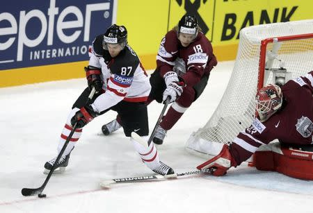 Canada's Crosby challenges Latvia's Abols and goalkeeper Mustukovs during their Ice Hockey World Championship game at O2 arena in Prague