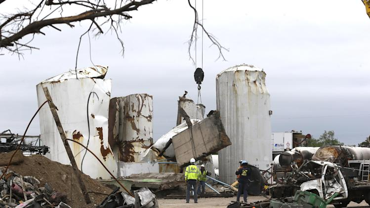 Investigators move and look through the debris of the destroyed fertilizer plant in West, Texas, Thursday, May 2, 2013. Investigators face a slew of challenges in figuring out what caused the explosion at the fertilizer plant that killed 14 people and destroyed part of the small Texas town. (AP Photo/LM Otero, Pool)