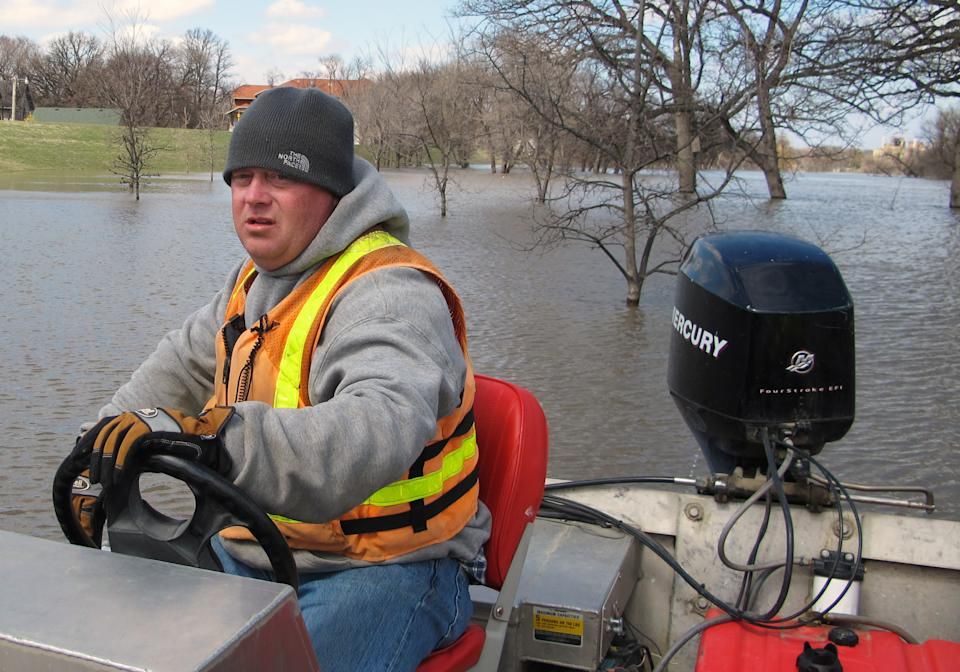 In this April 30, 2013 photo, Mike Andersen of the United States Geological Survey maneuvers a boat on the Red River in Fargo, N.D., so a USGA hydrologist can take stream flow measurements. Even with reams of data, forecasting a flood is still an imprecise science. (AP Photo/Dave Kolpack)