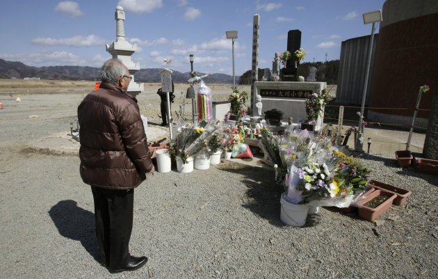 A man offers prayers in front of the main entrance of Okawa Elementary School where 74 of the 108 students went missing after the March 11 tsunami in Ishinomaki, Miyagi prefecture, Japan, Monday, Marc